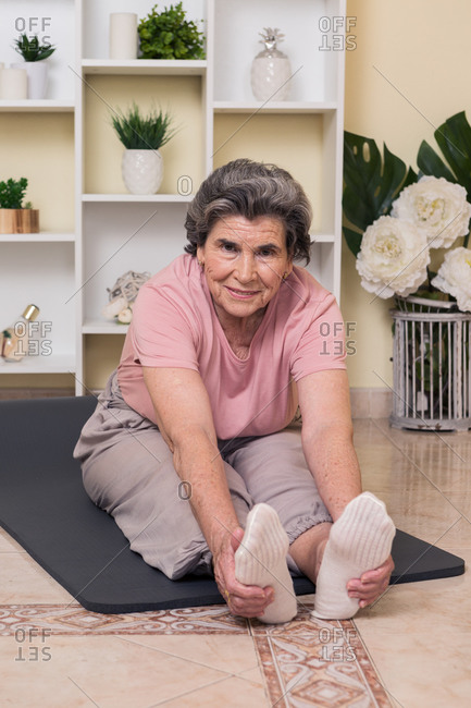 senior female in active wear sitting on mat near shelves with potted plants in room and doing stretching exercise while practicing yoga