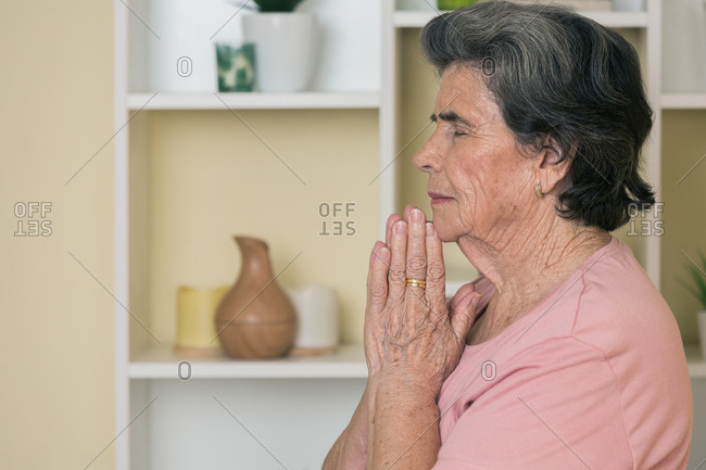 Concentrated senior female in active wear sitting on mat near shelves and meditating with closed eyes during yoga practice at home