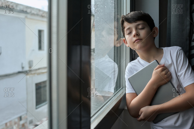 Side view of kid in casual wear browsing tablet while standing near window during quarantine