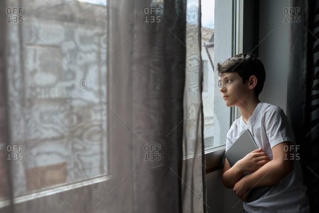 Thoughtful child in casual t shirt standing with tablet and leaning on window while observing rain in street