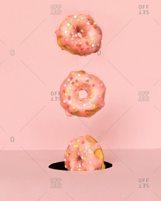 Bunch of tasty doughnuts with sweet icing falling into round hole on pink background