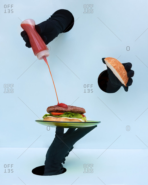 Hand of anonymous people in black gloves holding plate with burger and spilling ketchup on patty against blue background