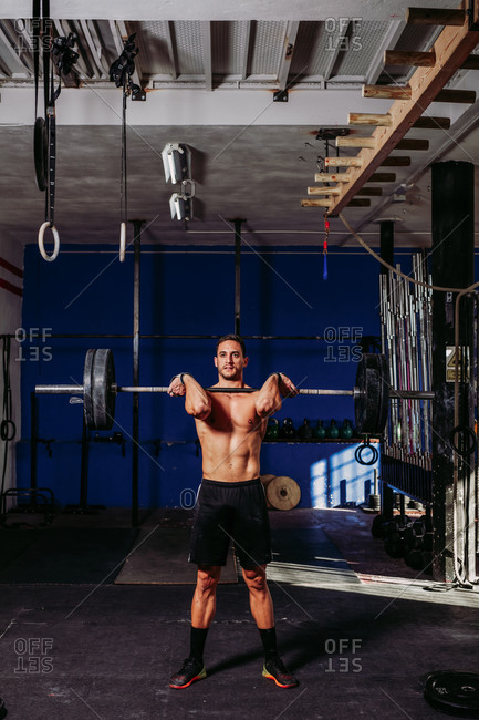 Athletic male with naked torso doing deadlift with heavy barbell while pumping muscles in sports center