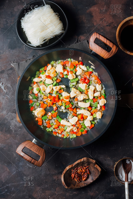 Top view of frying pan with chopped chicken and vegetables placed near bowl with uncooked rice noodles during food preparation