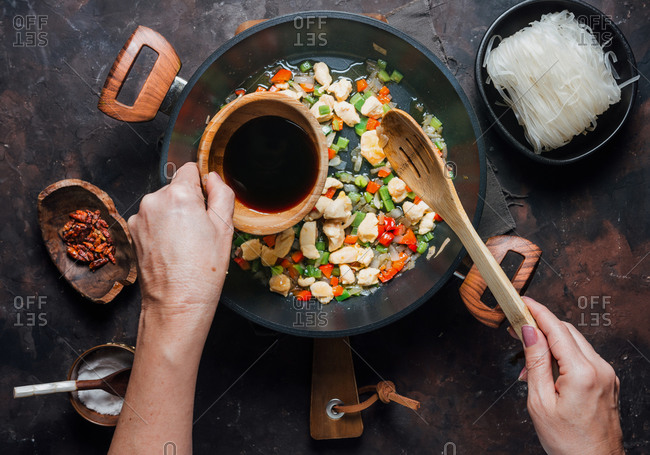 From above of crop anonymous woman pouring soy sauce into pan with chopped chicken and vegetables while preparing delicious noodles in kitchen