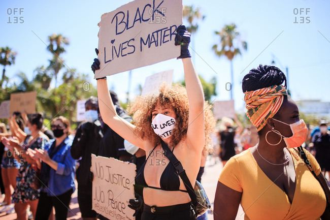 Serious ethnic female with afro hairstyle holding cardboard poster with black lives matter inscription during demonstration in crowded city and clapping