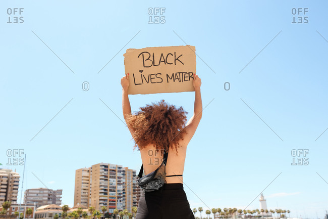 Back view of ethnic female with afro hairstyle standing with cardboard poster with black lives matter inscription during demonstration in front of sea