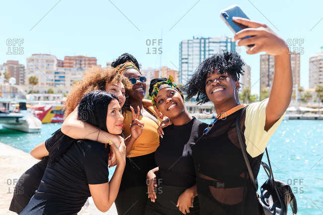 Group of charismatic multiracial girlfriends standing at waterfront and taking selfie on smartphone during stroll in summer