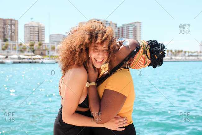 Side view of multiethnic female friends embracing and giggling in city on background of clear water of sea on sunny day