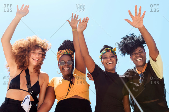 Low angle of company of friendly multiethnic females expressing joy with raised arms on background of cloudless sky in summer and looking at camera