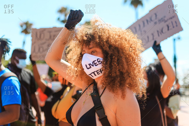 Ethnic female with afro hairstyle and in protective mask with black lives matter inscription standing on street raising fist during a demonstration