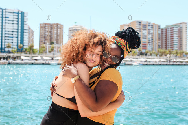 Side view of multiethnic female friends embracing in city on background of clear water of sea on sunny day