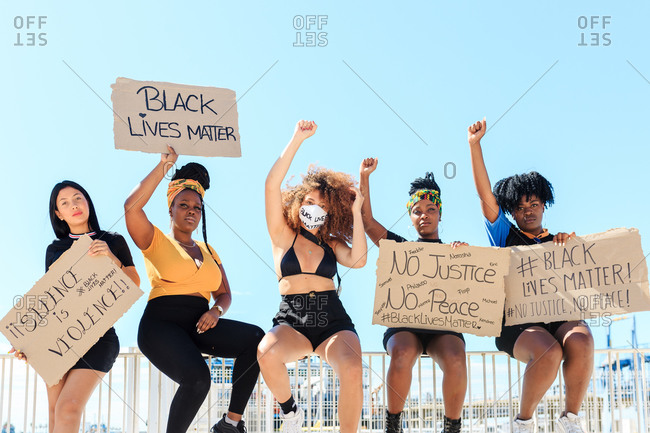 Group of multiethnic female activists protesting with raised arms in city with carton placards with black lives matter inscription and looking at camera
