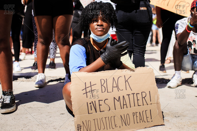 Serious ethnic female with afro hairstyle sitting on pavement with cardboard poster with black lives matter and no justice no peace inscription during demonstration in crowded city and clapping