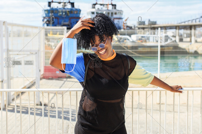 Delighted female in trendy wear and with afro hairstyle standing on quay with protective mask on sunny day and looking away