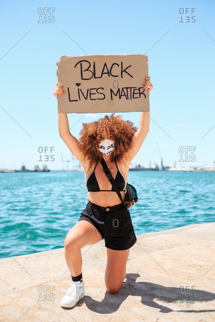Ethnic female activist in medical mask and with black lives matter placard taking knee in solidarity during peaceful protest in city and looking at camera