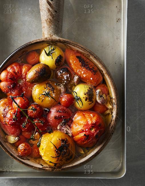 Confit tomato and garlic in ceramic pan