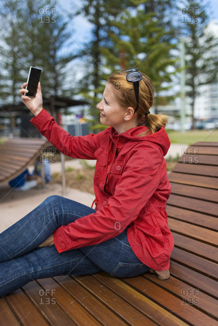 Woman taking selfie on a park bench in Maroochydore, Australia
