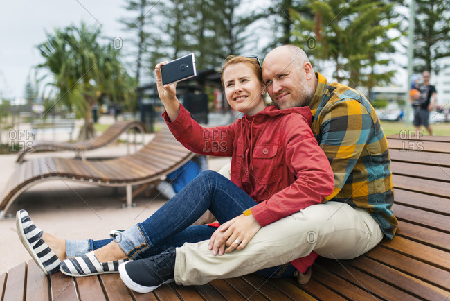Couple taking selfie on a park bench in Maroochydore, Australia