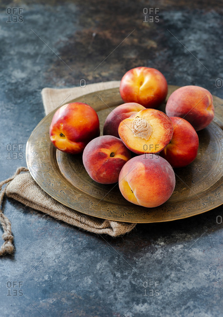 Peaches and nectarines on vintage tray over dark background