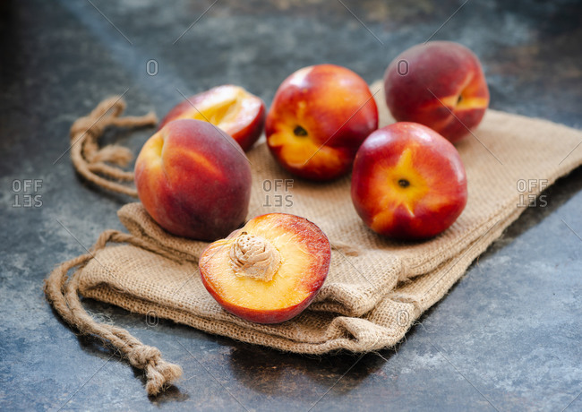 Peaches and nectarines on rustic napkin over dark background, closeup