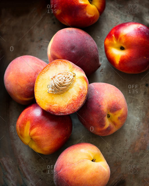 Peaches and nectarines on vintage metal background, top view, closeup