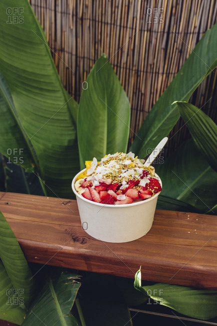 Acai bowl on wooden counter with red leaves