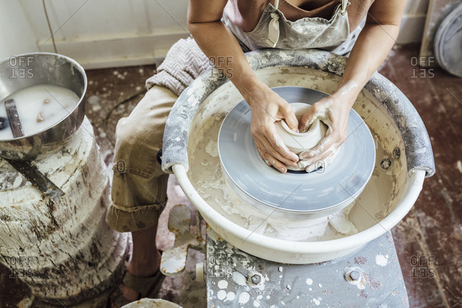 Woman making pottery on wheel from abovehorizontal
