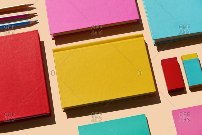high angle view of some notebooks, erasers and pencils of different colors on a pale pink background