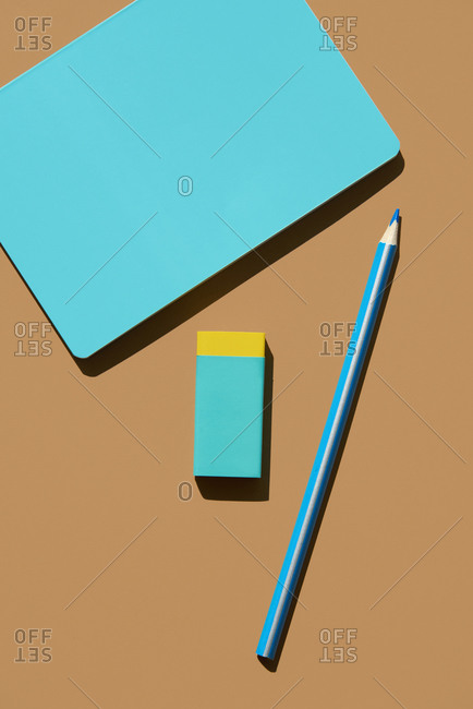 high angle view of a blue notebook, a blue and yellow eraser and a blue pencil on a brown background