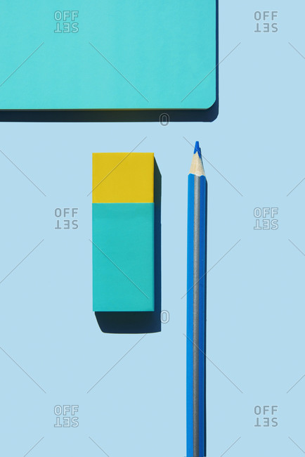 high angle view of a blue notebook, a blue and yellow eraser and a blue pencil on a blue background