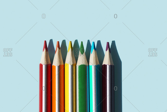 high angle view of some pencils, with the colors of the rainbow, on a blue background