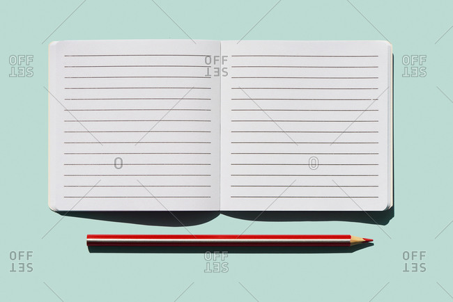 high angle view of a red pencil and a blank lined paper notebook open on a blue background