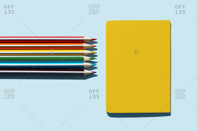 high angle view of a yellow notebook, and pencils of the colors of the rainbow, on a blue background