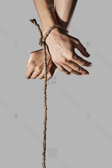 closeup of a man with his hands tied with rope on a gray background