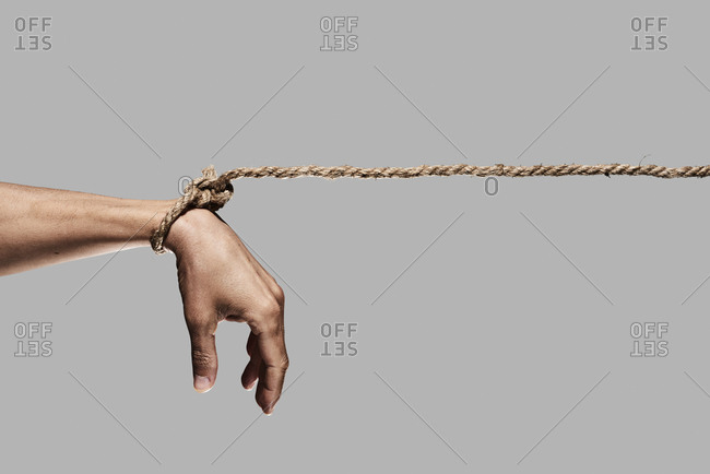 closeup of a man with his hand tied with rope on a gray background