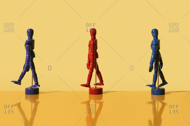 articulated dolls of different colors, keeping a distance, on a yellow background