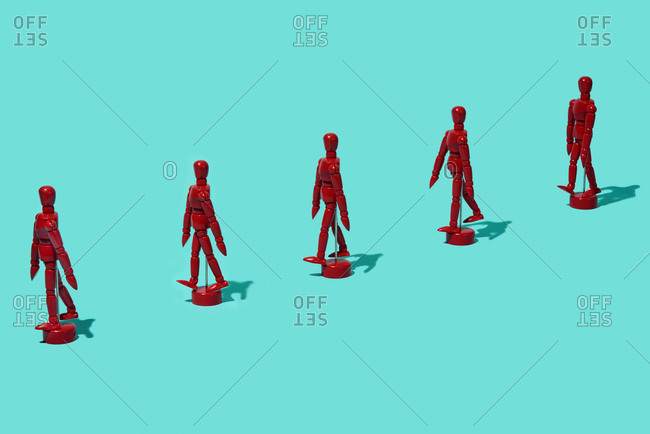 red articulated dolls, keeping a distance in line, on a blue background