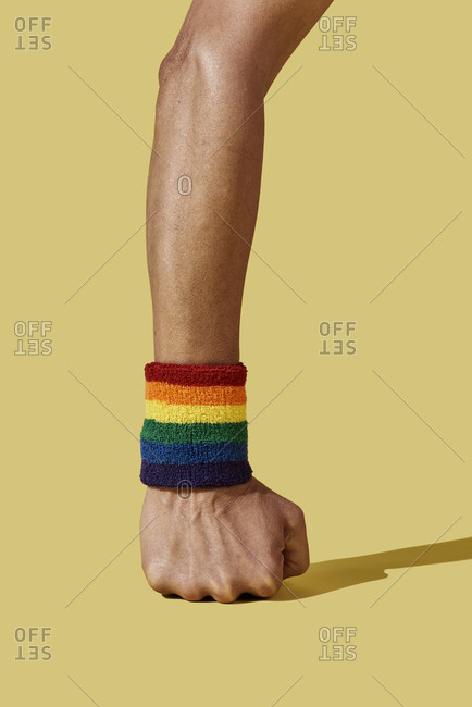 closeup of the arm of a young person wearing a rainbow-patterned wristband on a yellow background