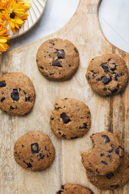 Top view of chocolate chip cookies on a wooden cutting board and orange flowers