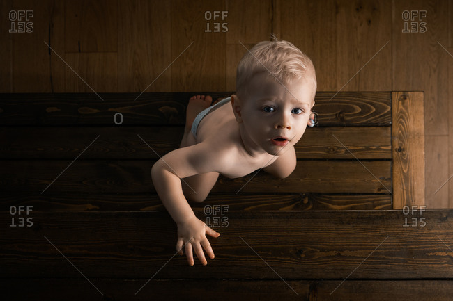 Overhead view of a blonde toddler boy climbing up on a wooden bench