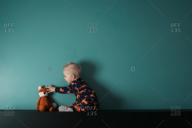 Blonde toddler in pajamas playing with stuffed fox in front of a blue wall