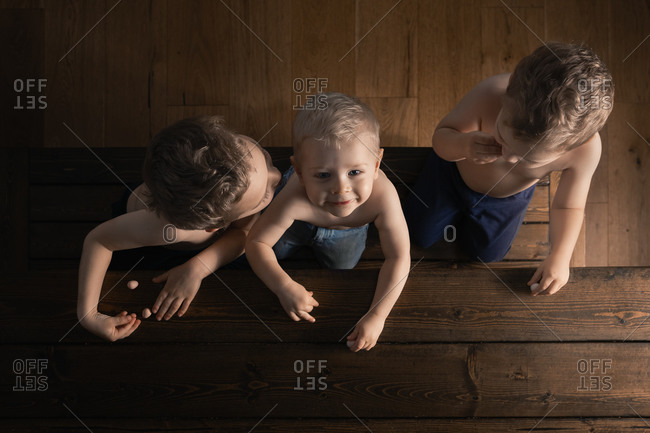 Overhead view of a three boys sitting on a wooden bench eating candy
