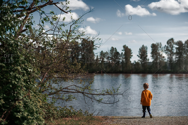 Little boy wearing a orange sweater looking out at lake