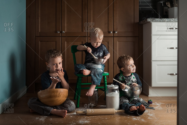 Three little boys making a huge mess in the kitchen while baking