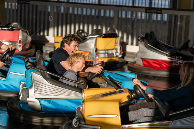Father and son riding in bumper cars at a fair