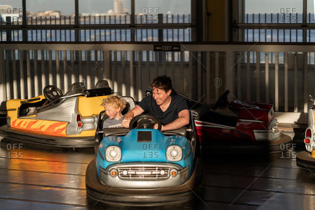 Father and son riding in bumper cars at an amusement park