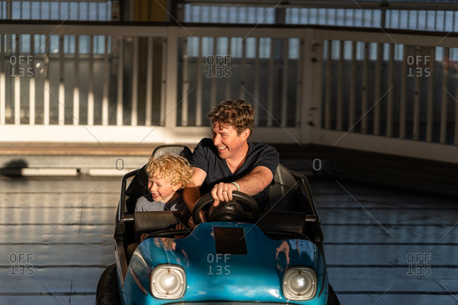 Father and son riding in a bumper car at an amusement park