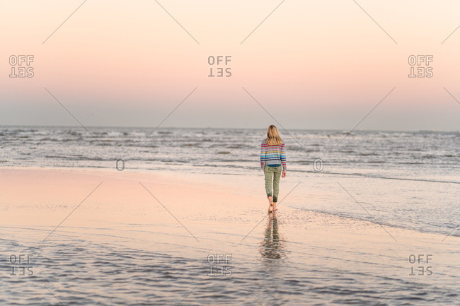 Blonde preteen girl walking on a beach under purple sunset sky
