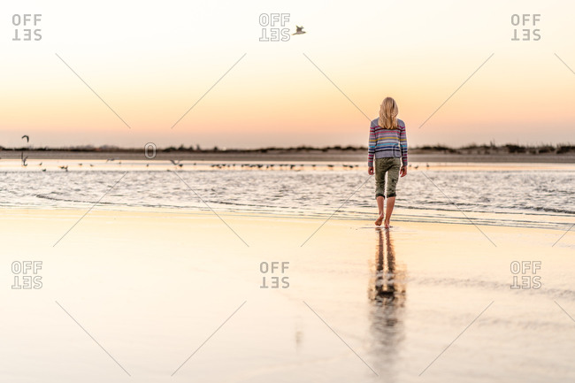 Blond girl walking on a beach under sunset sky